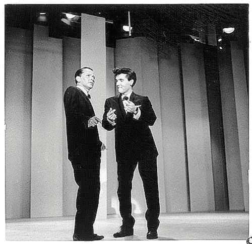 Elvis Presley snapping his fingers and swinging on stage with Frank Sinatra