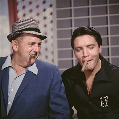 Colonel Tom Parker and Elvis Presley playing with his cigar