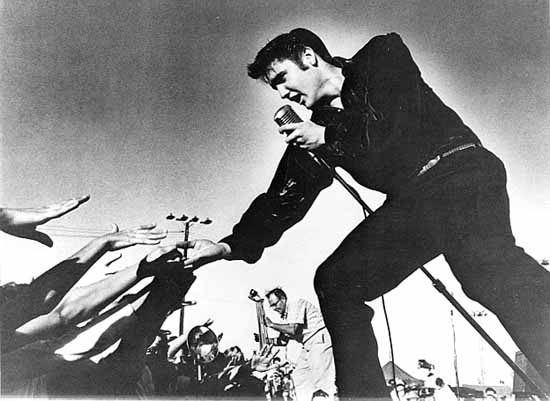 Elvis Presley touches his adoring fans