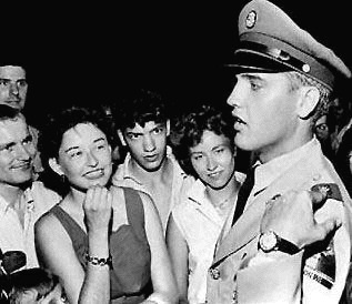 Elvis Presley in his army dress uniform greeting a crowd of fans