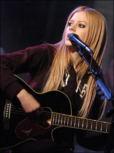 Avril Lavigne sitting down playing acoustic guitar
